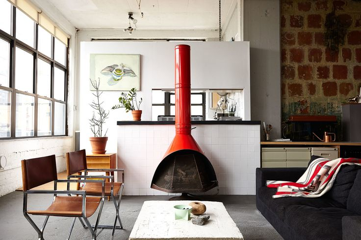 """""""I'm not trying to hide anything. I wanted to stay true to the industrial look,"""" explains Owen Wright, the owner of this Brooklyn loft. Owen works with his building's landlord and consequently has accrued countless pieces of furniture from both former tenants and Craigslist—including this 1960's fireplace and pair of steel frame chairs Owen had reupholstered. A BoConcept sofa and coffee table Owen constructed himself complete the living room."""