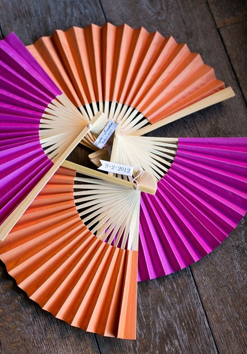 Pink and orange wedding fans with custom tag for guests at outdoor wedding ceremony
