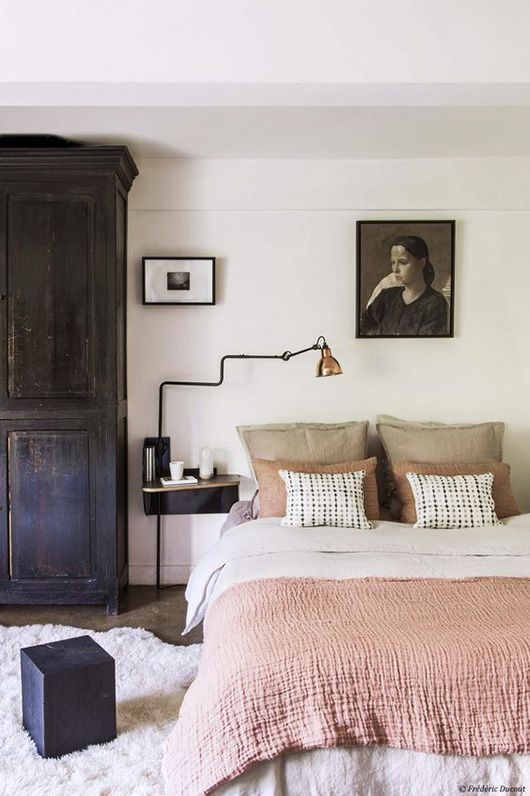 Tonal bedroom in shades of nude, beige and powder pink as seen on sfgirlbybay   black wood armoire   industrial style wall sconce   black and white portrait painting   Get the look with cushion covers and a Loose Fit bedspread from Bemz