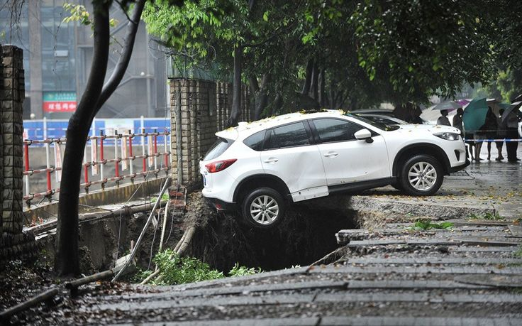 A white SUV dangles in mid-air after a 7-metre-deep pothole opened up after heavy rainfall in Chengdu city, Sichuan province, China. According to staff at a nearby construction site the surface of the foundation was damaged, causing an embankment cave-in. With a loud bang, the parked Mercedes, Audi, BMW and other luxurious cars plummeted and crashed into the seven-meter deep pit, witnesses said.