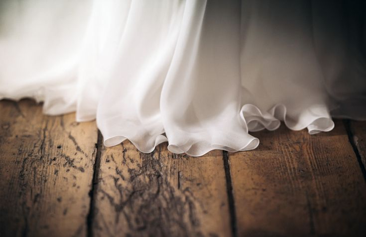 The soft flowing hemline of the dress against the aged wooden floors. Wedding prep' in the beautiful light, colour and tones of Villa Parma in Daylesford.  www.shaunguestphotography.com.au