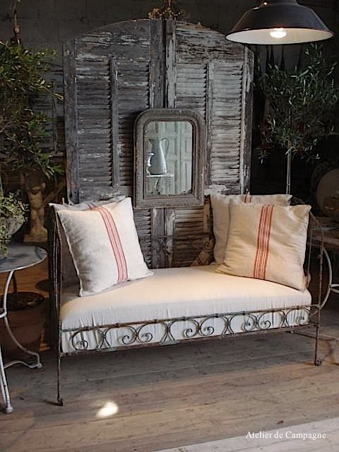 Cool Place To Nap...Shutter doors..looks like origional paint..or lack of paint...displayed behind metal settee..with mirror hanging on shutter...