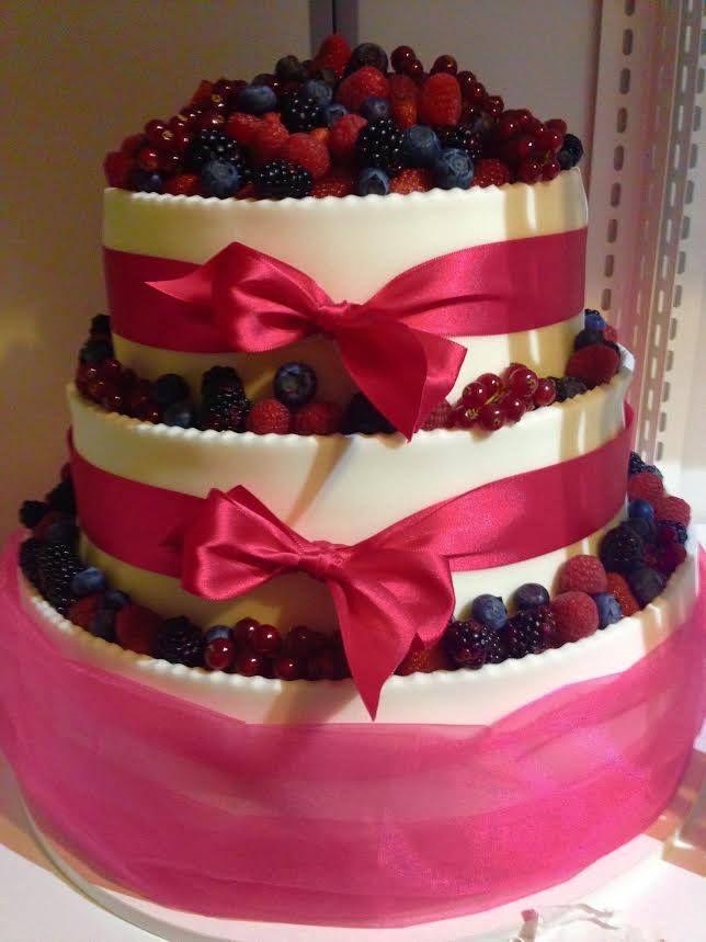 Třípatrový svatební dort ozdobený bílým fondánem, saténovými stuhami, organzou a čerstvým ovocem