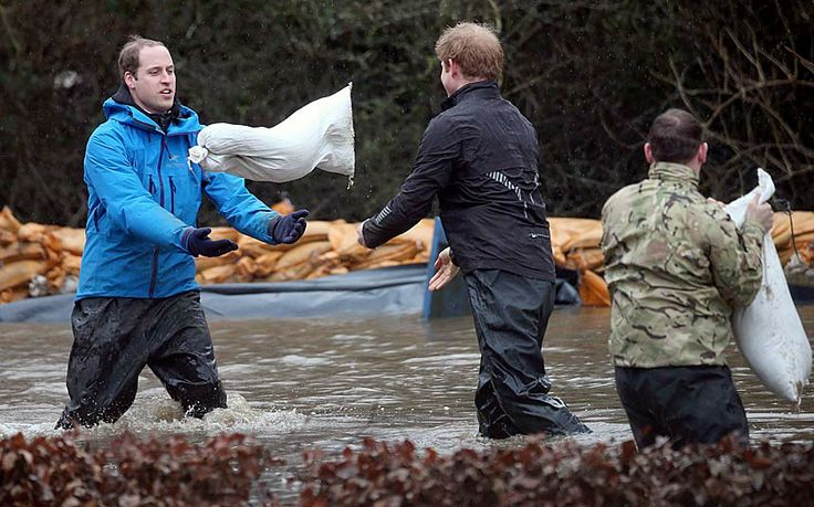 Prince Harry (centre) throws a sandbag to his brother Prince WIlliam as they help with flood protection