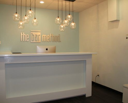 Reception desk with logo feature wall. Pendant lighting above desk.