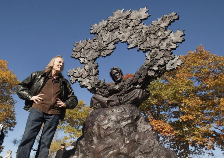 Gordon Lightfoot poses with a bronze statue in his honour at Barnfield Point, on the Gordon Lightfoot Trail in Orillia, Ont., on Friday, October 23, 2015.
