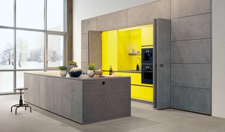 Concrete kitchen with yellow interiors: Real concrete filler applied exclusively by hand – each element is unique. Sealed to be entirely suitable for kitchen life. The monumental wall surface is divided into horizontally arranged panel elements and vertically running front elements. Matching the worktop in quartz tone in tone. The skilful contrast to the kitchen, hidden by the rear sliding folding doors in striking zinc yellow lacquer, is also well worth seeing.