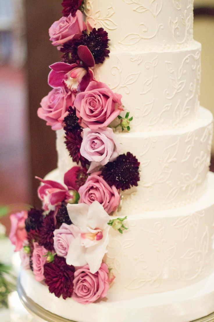 cascade of lavender, purple and burgundy flowers on the wedding cake include ranunculus, scabiosa, orchids and roses.