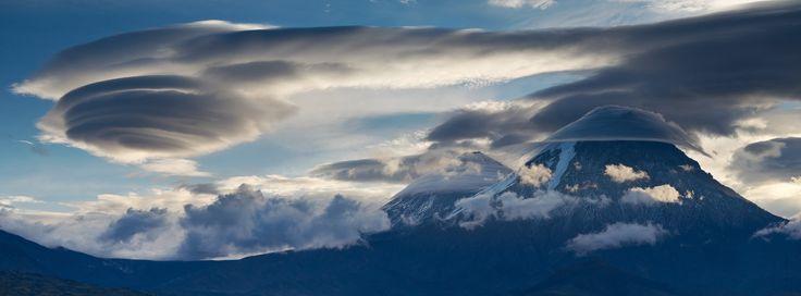 ロシアのアルタイ山脈でみられた多様なレンズ雲の写真。ロール状と山頂に懸かる傘状という二種類があり、後者は斜面から少し浮いたもの(手前)と斜面に貼り付いたもの(奥)の二つを含む。ロシアの写真家 A. Ermolitskii 氏が撮影。