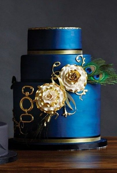 Pantone's snorkel blue wedding inspiration with a gold and snorkel blue three tiered wedding cake complete with painted flowers and peacock feathers.