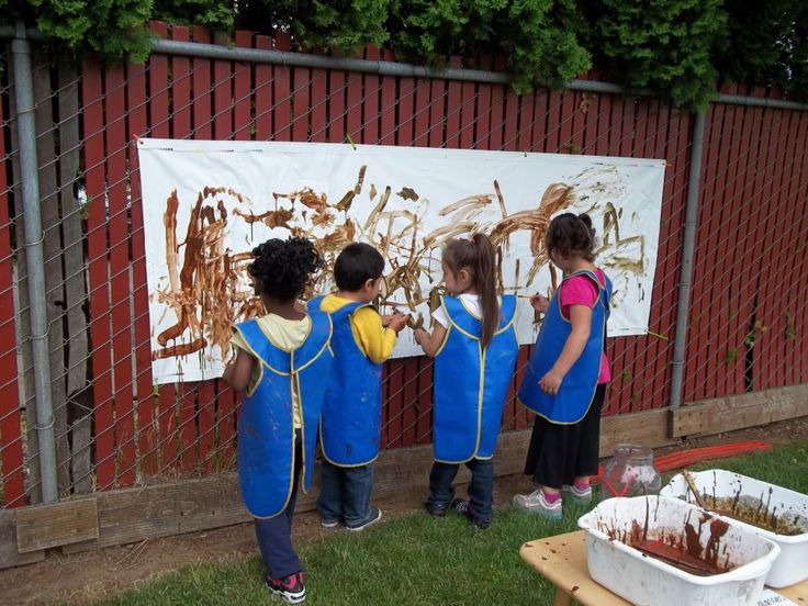 Mud Art: Some KinderCare students celebrating International Mud Day at school. The students painted outside using .... mud.