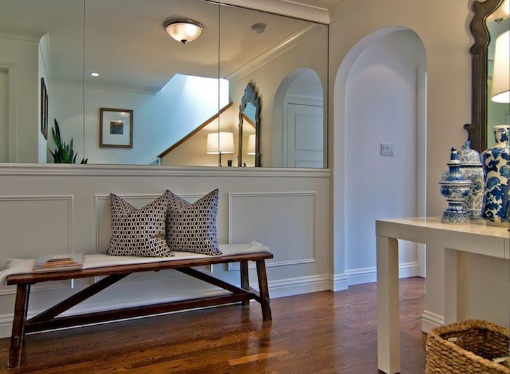 Delightful Foyer Space With Mirrored Walls And Wainscoting