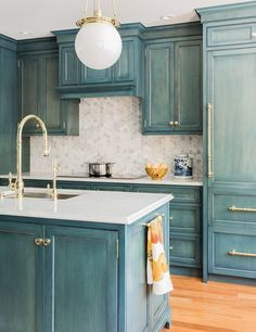 Vintage Blue Painted Cabinets with White Marble Countertop and Hexagonal Backsplash.
