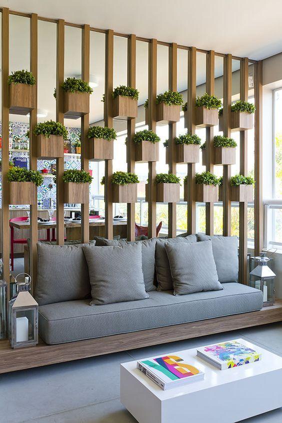 Painel dividindo ambientes em varanda gourmet com cachepós para plantas.