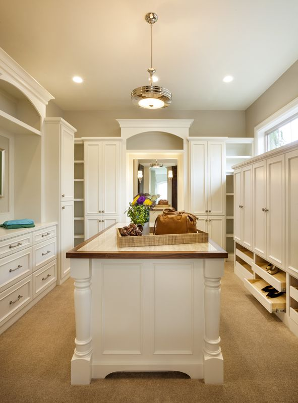 The walk-in closet has drawers for shoe storage, a storage island in the center, and full length mirrors on the back wall.