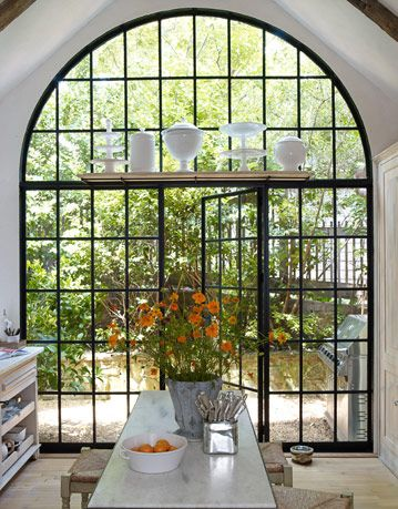 Lately, I've been loving the look of industrial windows in traditional homes... love this arch with a platform for display.