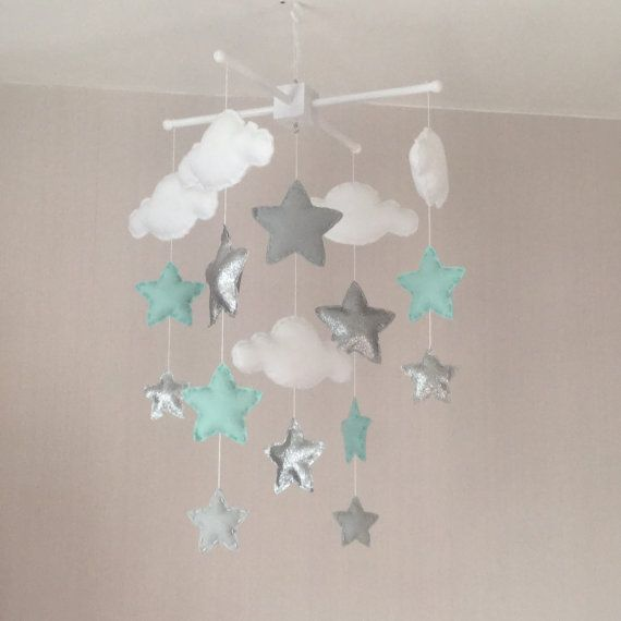 Clouds and stars baby crib mobile. An ideal gift for a new babys nursery or for room decor in an older childs bedroom. This mobile consists of five white clouds and twelve stars (pale grey, pale mint green and twinkling glittery silver )in three sizes. The elements are suspended with white thread from either a natural wood or a white wooden mobile hanger. Each element is created with felt and entirely hand sewn. The clouds and stars are lightly stuffed with hypo-allergenic polyester…