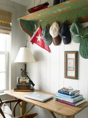 The home office reflects a love of sailing through a vintage nautical lamp, a Nantucket Alerion Fleet racing pennant, and hats from sailing clubs around the world. The weathered pine desk was once a tavern table.