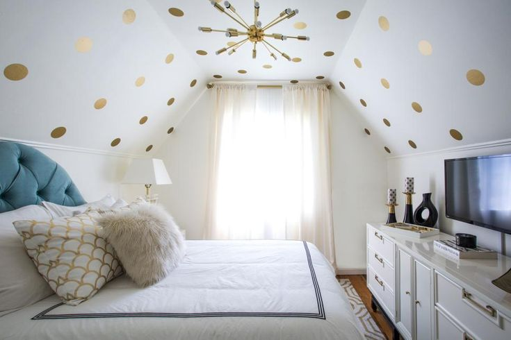Glamorous gold polka dots draw the eye upward in this odd-shaped bedroom, helping to elevate the appearance of the ceiling. White walls, white furniture and a window make the small but stylish space feel brighter and larger.