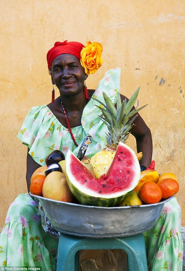 Local flourishes: A woman sells fruit in Cartagena's old quarter.
