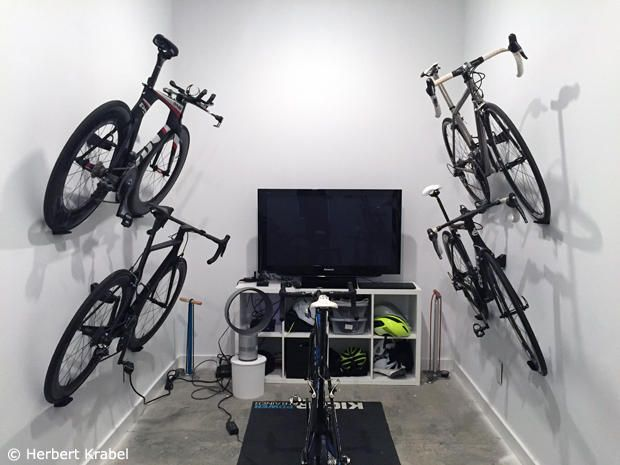 It is fairly simple to hang the bikes once the mount is installed, however a second set of hands is helpful when initially attaching the Cycloc Hero to the wall. We could have mounted 3 bikes on top of each other in this tall space, but decided to keep them within arms reach instead. The Ikea shelf under the TV helps store bike shoes, helmets, gear and various electronics. The Wahoo Kickr has been my go to trainer for about a year now and it fits in well in the new space.