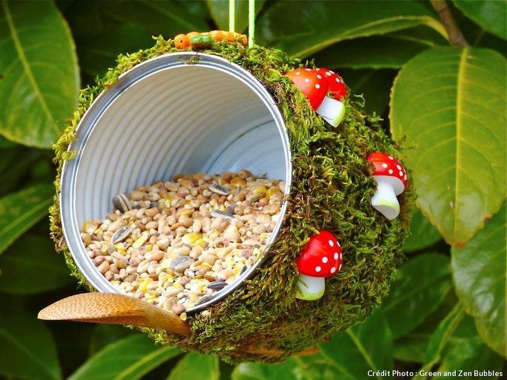 Mangeoire pour oiseau à suspendre faite avec une boite de conserve et une spatule en bois. Elle est recouverte de mousse et ornée de champignons en plastique.