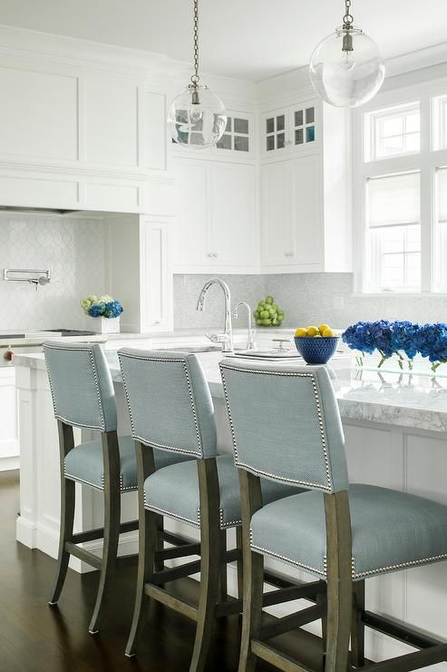 Two clear glass globe light pendants illuminate a white kitchen island topped with White American Quartzite fitted with a prep sink and gooseneck faucet lined with powder blue counter stools finished with silver nailhead trim.