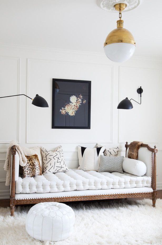 White vintage canapé couch | patterned mix matched pillows | neutral color scheme | white wooden paneled walls