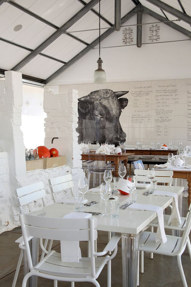 Gorgeous restaurant interior in white and black with white brick walls. This place is called Babylonstoren and is located in South Africa.