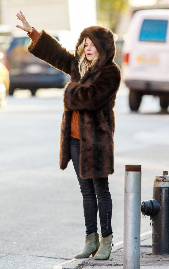 Sienna Miller - Actress Sienna Miller hails as cab bundled up wearing a hooded fur coat in New York City