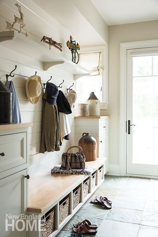 Charming and rustic country house entryway with slate floors, built-in storage benches and white shiplap walls.