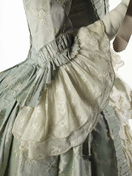 Dress, flounce and ruche detail of 1760s made gown of very fine silk (lustring). The small flower pattern in off-white woven into the pale blue background suggests a date of around 1755 for the fabric, though the gown was made possibly a decade later. Museum of London