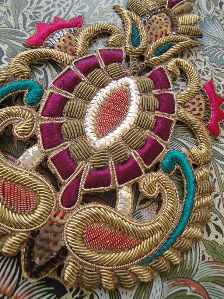 Colourful goldwork embroidery close-up, detail: Hand embroidered motif for embellishment of clothing, costumes, decor, accessories.  Made with gold bullion and silk on canvas.