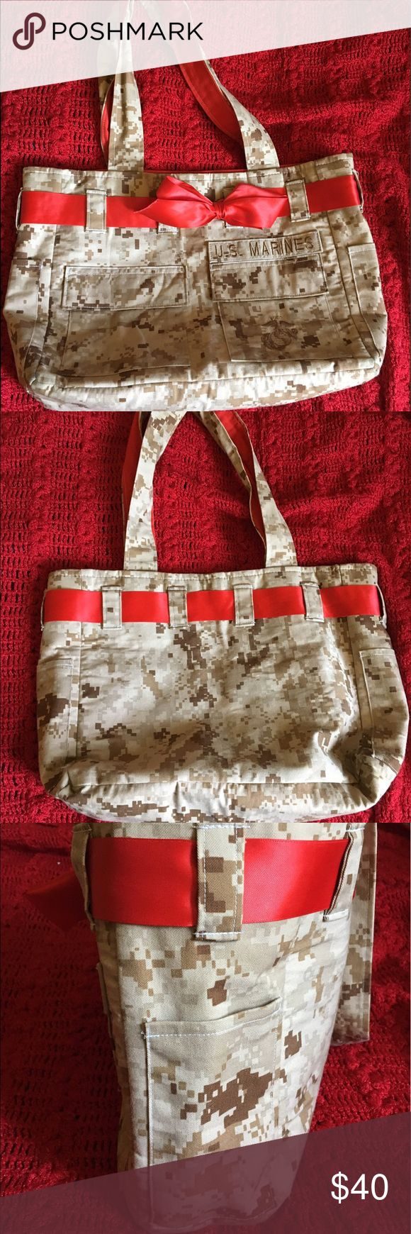 USMC Tote Custom made USMC tote. 4 inside pocket, 2 side pockets. Red ribbon bow goes all around the tote and is changeable(not sewn on). The two front pockets are just a design not actual pockets. Has U.S. Marines patch on the right side of the front. Room available to add your loved ones name on the left. Made with Desert Camo Uniform. Perfectly hand made. Clean and perfect condition.  It was barely used. NO TRADES, NO OFFERS!! PRICE IS FIRM. Bags Totes