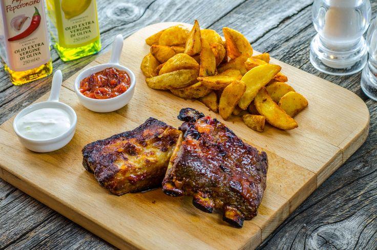 Costițe de porc marinate servite cu cartofi wedges, maioneză cu usturoi și sos BBQ