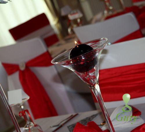 Guľatá čierna sviečka na svadbu v martini dekoračnom skle s červenými perličkami.