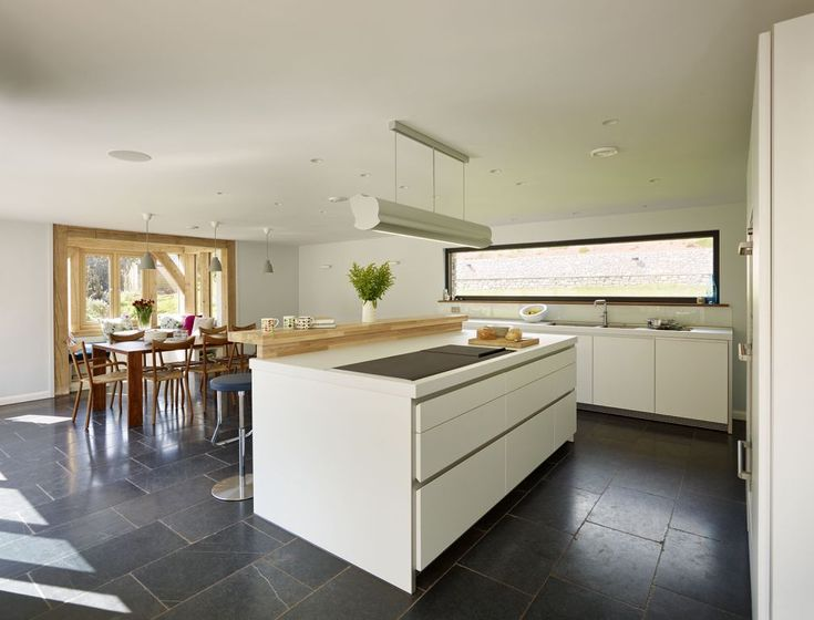 Contemporary country kitchen - White bulthaup b1 open plan kitchen with centre island, dark grey slate floor and stylish extraction. This modern kitchen design includes a central cooking area with and elegant overhead extractor hood. South Devon Kitchen Project | Sapphire Spaces