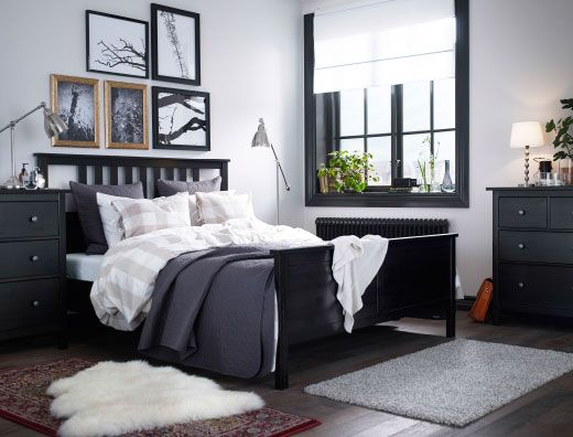 Black trims!  A large bedroom with a black-brown bed with bed textiles in beige/white and dakr grey. Combined with black-brown chest of drawers and lamps in nickel-plated steel.