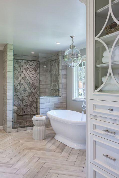 Master bathroom with herringbone tile on floor, freestanding tub and walk in shower   Artistic Tile & Stone