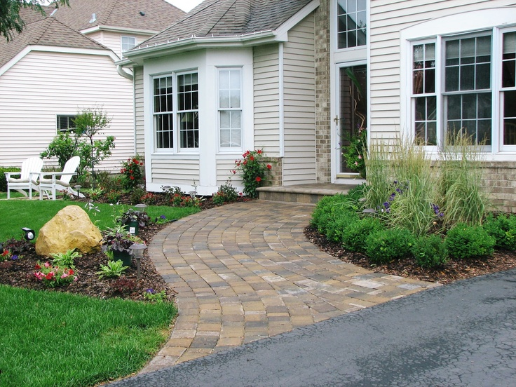 a wide curved paver walkway and plantings create a much more welcoming entrance