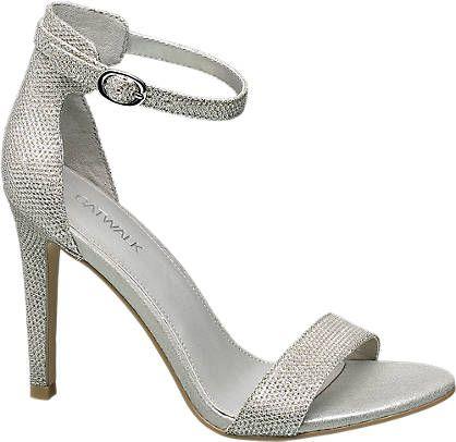 Ein optischer Hingucker ist die silberne Sandalette von Catwalk. Durch die angesagt, silberglänzende Optik und den 10,3 cm Pfennigabsatz ist der Schuh ein Highlight für jedes Partyoutfit. Ein breiter Riemen am Spann, sowie ein schmaler, verstellbarer Riemen am Knöchel runden den Look ideal ab. Der geschlossene Fersenbereich und die beiden Riemen der Sandalette bieten dem offenen Schuh seinen Halt.