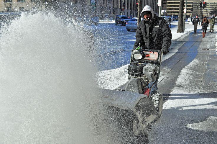 Seorang petugas membersihkan salju di trotoar setelah salju turun di Washington D.C.