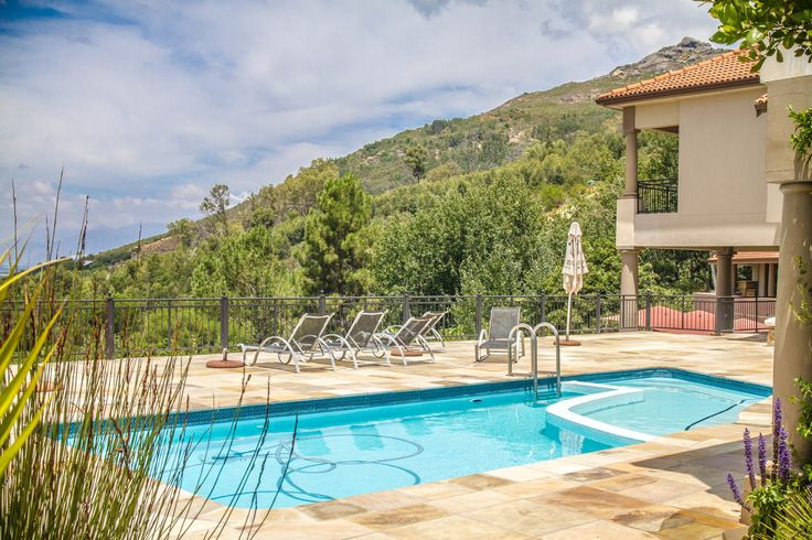 Sandstone tiles around the large swimming pool of this Paarl home for sale.