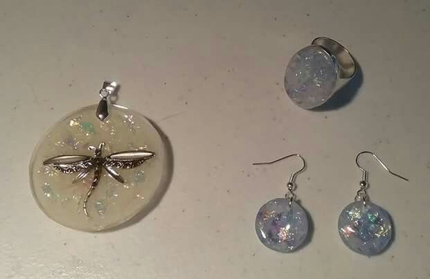 Resin jewellery. I added a broken Dragonfly pendant to resin with a drop of white paint and some chopped up cellophane pieces for the pendant. The ring and ear rings are clear resin with lots of chopped up cellophane.