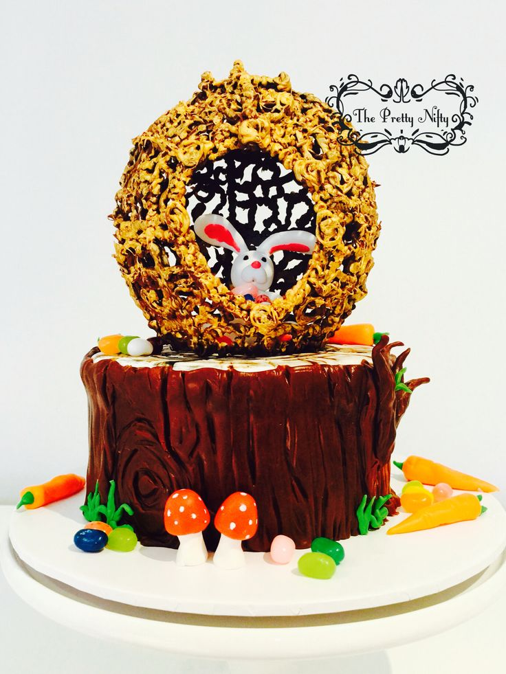 """No excuse for cake. It's Easter!  So here's """"Bunny in the Golden Egg.""""  This little bunny has collected all the Easter eggs and hides in his golden egg abode over the tree stump :D  Tree stump is made from chocolate fondant. Golden egg is piped chocolate and painted in edible gold."""