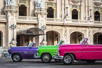 Kuba drei farbenfrohe amerikanische Oldtimer parken in Reihe vor dem Gran Teatro in Havanna
