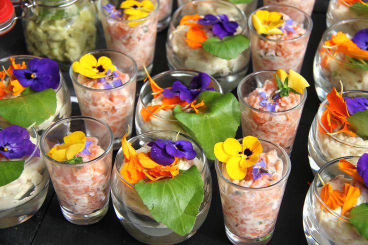 Glaasjes met eetbare bloemetjes en salade van gerookte paling, aardappel en waterkers / zalmtartaar, kappertjes, sjalotjes, limoen