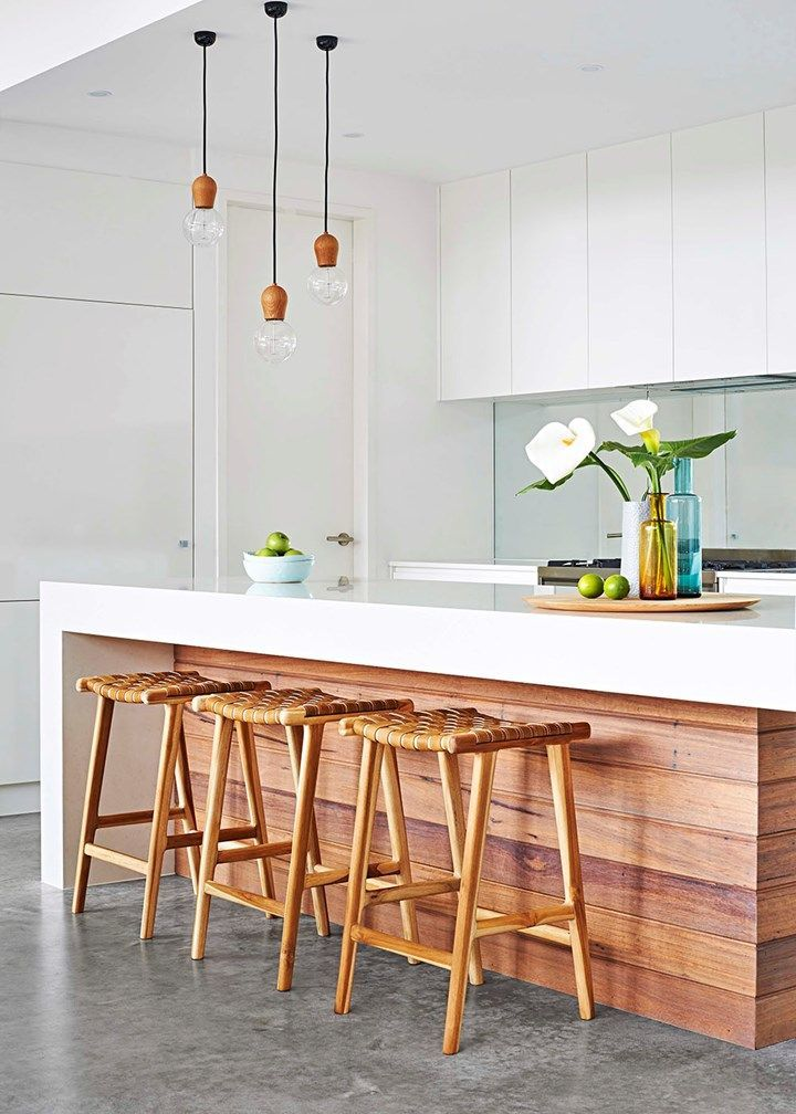 Here, the timber fascia, stools and light fittings give this kitchen truly standout looks – the woven seats add texture and the subtle touches of colour in the glassware are soft and inviting   Home Beautiful Magazine Australia