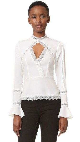 Tonal lace trim complements the Victorian-inspired look of this Nicholas blouse. Sheer insets and a center cutout reveal peeks of skin. The peplum hem and split, flared cuffs create a feminine profile. Long sleeves. Hidden back zip.