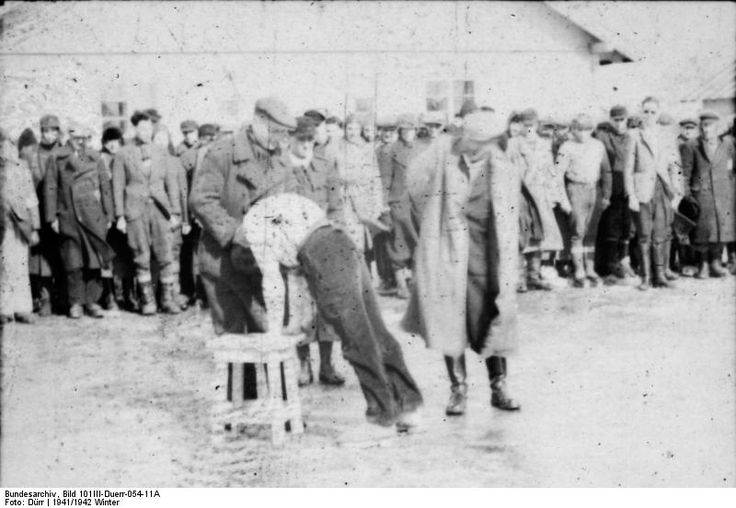 Latvia – Salaspils Concentration Camp, a Jew being beaten in front of other prisoners.